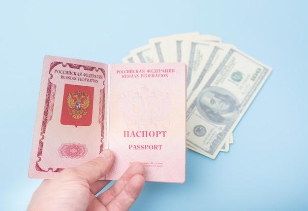 Otwórz rosyjski paszport międzynarodowy w ręce mężczyzny. dolary niebieski