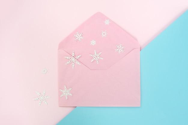 Otwórz różową kopertę z płatkiem śniegu na różowym i niebieskim