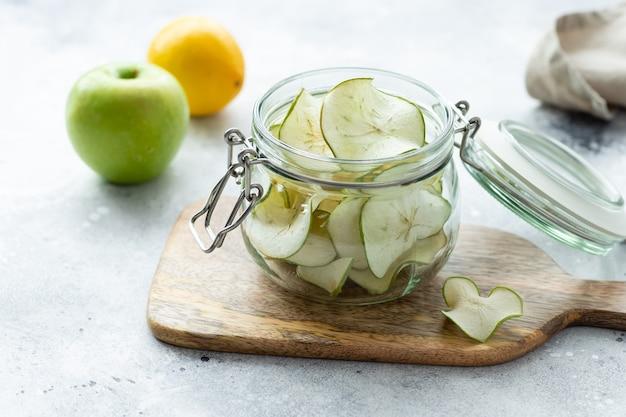 Otwórz słoik z chipsami jabłkowymi na drewnianej desce