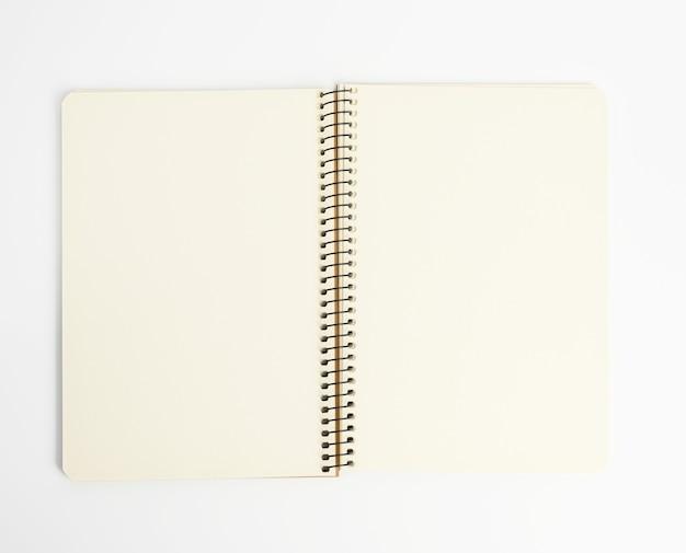 Otwórz spiralny notatnik z pustymi białymi arkuszami na białym tle, z bliska