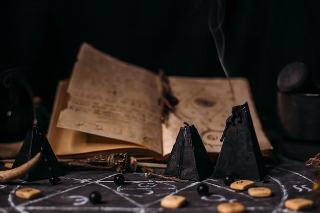 Otwórz starą książkę z czarami, runami, czarnymi świecami na stole czarownicy. koncepcja okultystyczna, ezoteryczna, wróżbiarska i wicca. scena halloween