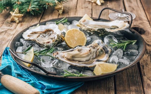 Otwórz surowe ostrygi z cytryną i rozmarynem. świeże owoce morza na metalowej tacy na rustykalnym drewnianym tle. ozdoby świąteczne