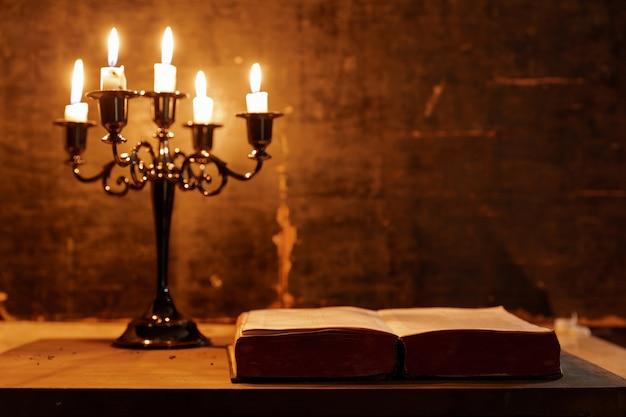 Otwórz świętą biblię i świecę na starym dębowym drewnianym stole. piękne złote tło. koncepcja religii.