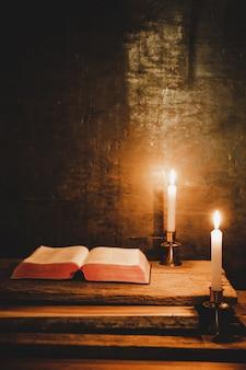 Otwórz świętą biblię i świecę na starym dębowym drewnianym stole.