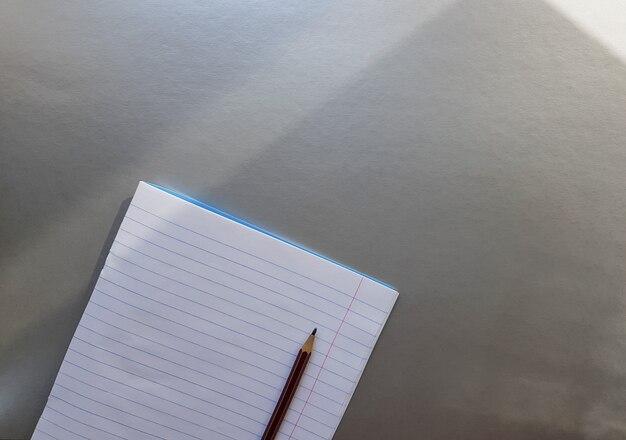 Otwórz szkolny notatnik z piórem na szarym biurku z promieniami słońca z okna. czysta, biała kartka zeszytu do pisania. koncepcja edukacji. skopiuj miejsce. widok z góry. leżał płasko.