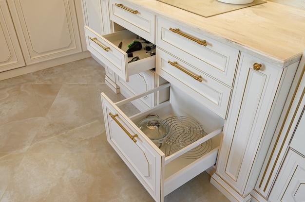 Otwórz szufladę w szafce na luksusowe beżowe i złote klasyczne meble kuchenne