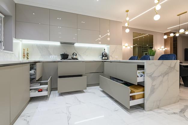 Otwórz szuflady w nowoczesnych białych meblach kuchennych