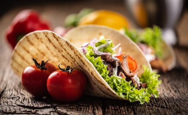 Otwórz tortillę mięsno-warzywną na rustykalnej drewnianej desce.