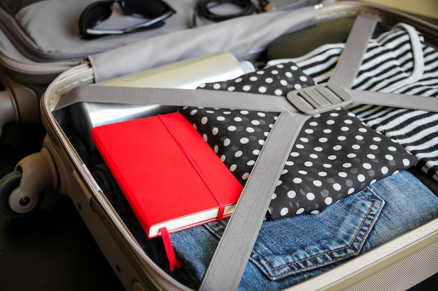 Otwórz walizkę podróżną pełną ubrań na czarnym tle