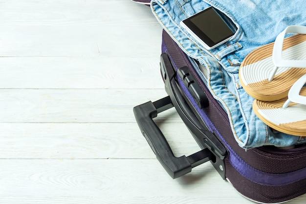 Otwórz walizkę z akcesoriami podróżnymi na białym drewnianym stole