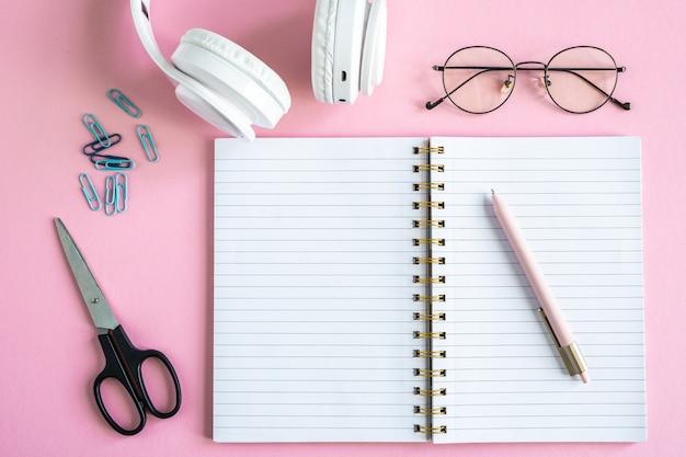 Otwórz zeszyt za pomocą pióra, okularów, nożyczek, spinaczy i słuchawek na różowym tle