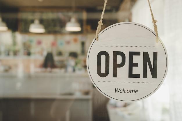 Otwórz znak kawiarni wiszący na szklanych drzwiach
