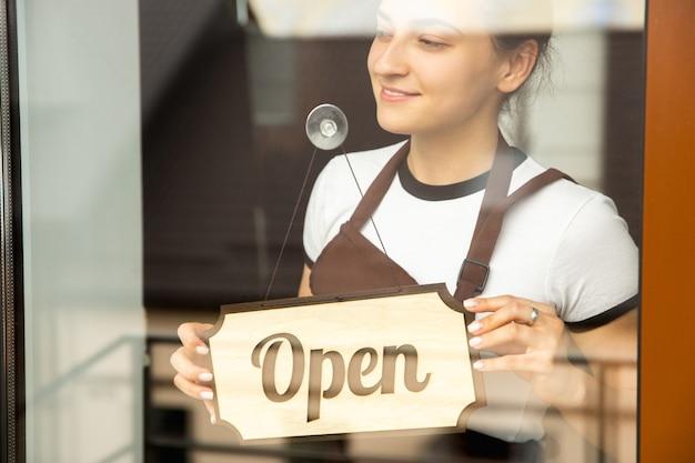 Otwórz znak na szkle z odbiciem ulicznej kawiarni lub restauracji. pandemia koronawirusa nowe zasady bezpieczeństwa. otwarcie po czasie kwarantanny. odzyskiwanie małych firm po izolacji. ścieśniać.