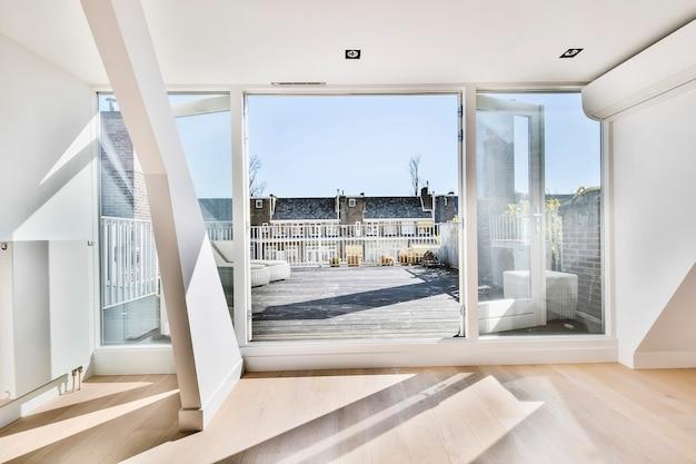 Otworzone szklane drzwi prowadzą na taras z drewnianymi deskami i leżakami w jasnym świetle słonecznym