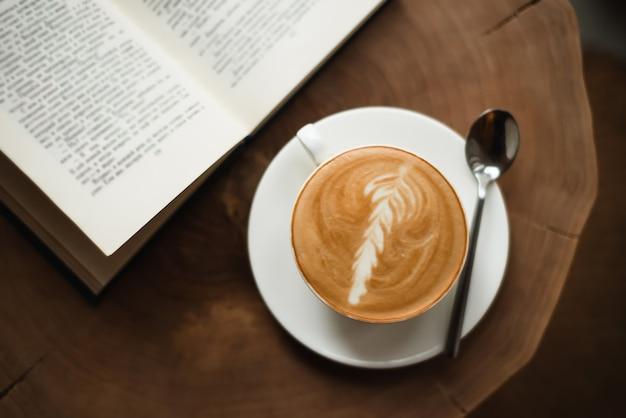 Otworzył książkę i filiżankę kawy na drewnianym stole.