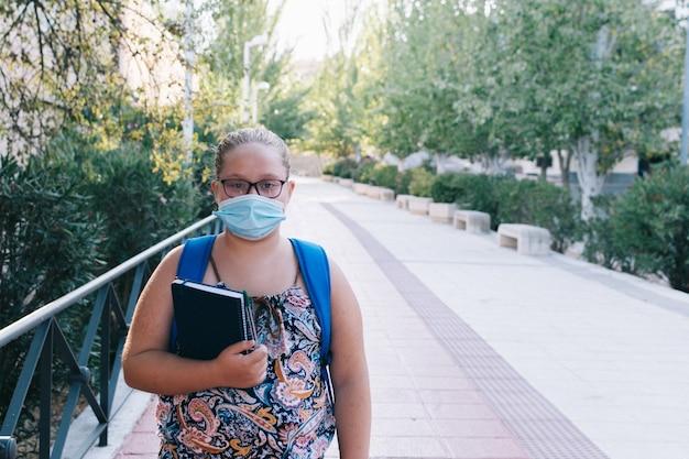 Otyła blondynka w okularach, niebieskim plecaku i masce w drodze do szkoły