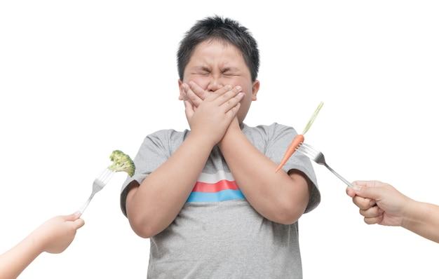 Otyła gruba chłopiec z wyrażeniem obmierzłość przeciw warzywom odizolowywającym na białym tle, odmawia f