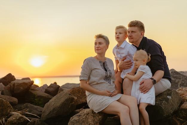 Otyła kaukaska rodzina kobieta w ciąży i jej mąż całują się, a dzieci dziecko cieszą się zachodem słońca na be