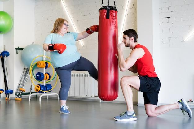 Otyła kobieta pracująca z trenerem