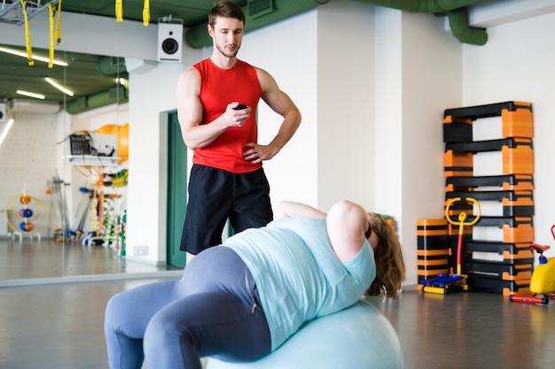 Otyła kobieta trenuje w klubie fitness