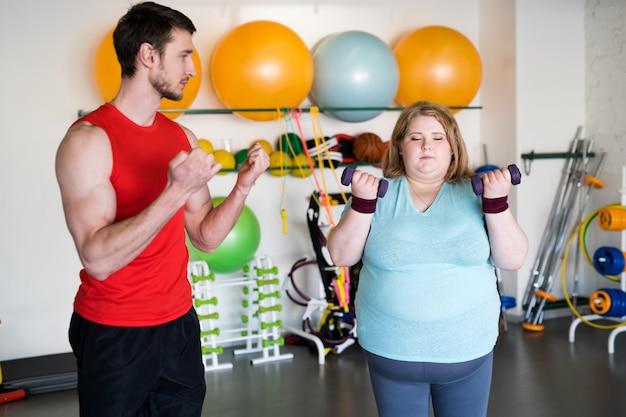Otyła kobieta w treningu na siłowni