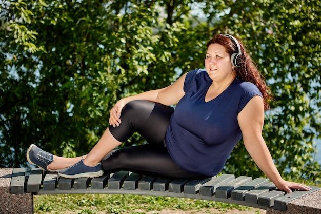 Otyła kobieta z ciałem plus size słucha muzyki przez bezprzewodowe słuchawki