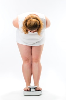 Otyła młoda kobieta stojąca na skali