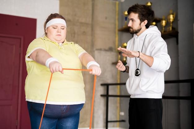 Otyła młoda kobieta szkolenia z instruktorem