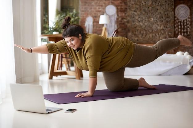 Otyła, pulchna młoda europejka z węzłem na włosach ćwiczy jogę lub pilates w pomieszczeniu na macie, wykonuje ćwiczenia wzmacniające mięśnie brzucha, ogląda lekcje wideo online przed otwartym laptopem na podłodze
