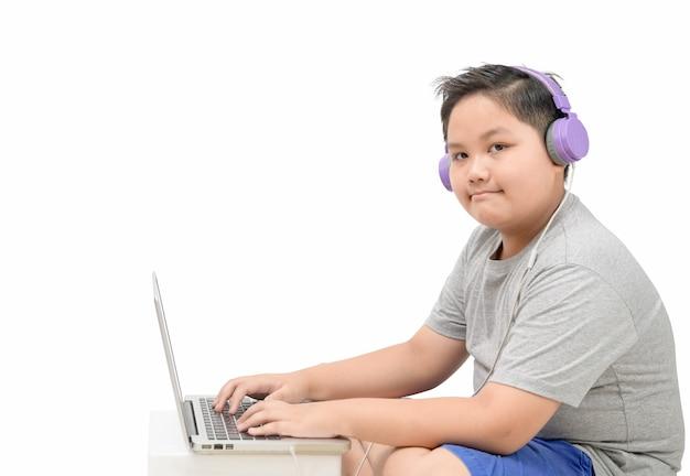 Otyłej chłopiec odzieży studenckiej hełmofonu nauka online z nauczycielem odizolowywającym