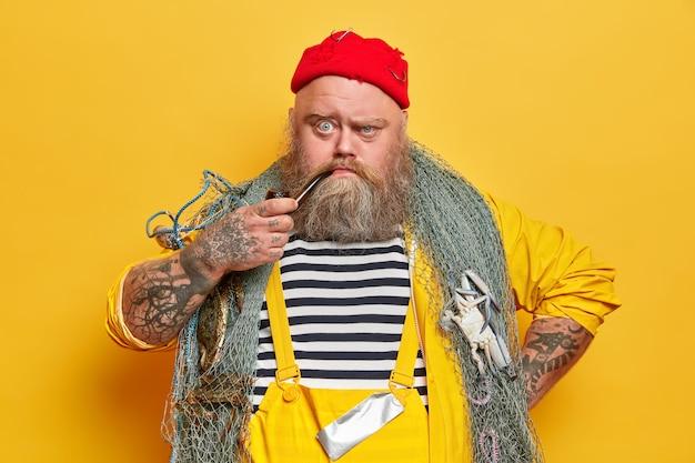 Otyły brodaty żeglarz męski z siecią rybacką