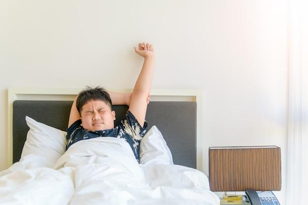 Otyły chłopiec budzi się rano i wyciąga rękę na łóżku. leniwa koncepcja