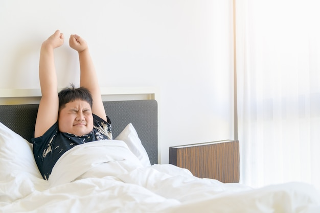 Otyły chłopiec budzi się rano i wyciąga rękę na łóżku. leniwy i odpoczynek