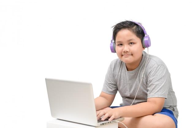 Otyły chłopiec student nosi słuchawki do nauki online w domu