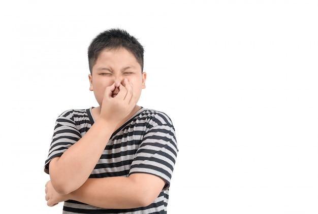 Otyły chłopiec trzyma nos z powodu nieprzyjemnego zapachu