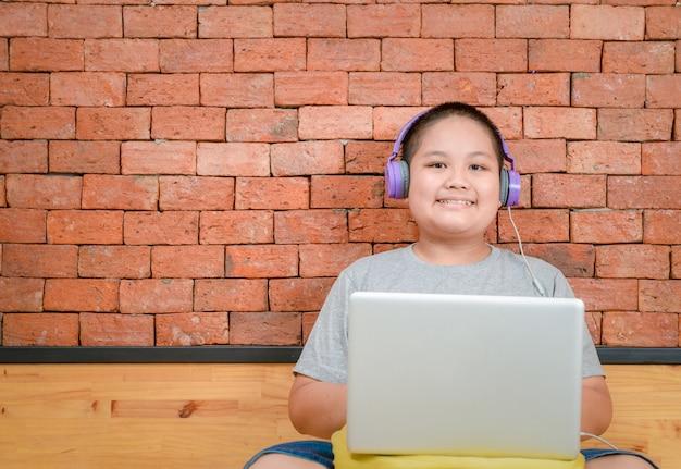 Otyły chłopiec uczeń nosi słuchawki do nauki online z nauczycielem w domu,