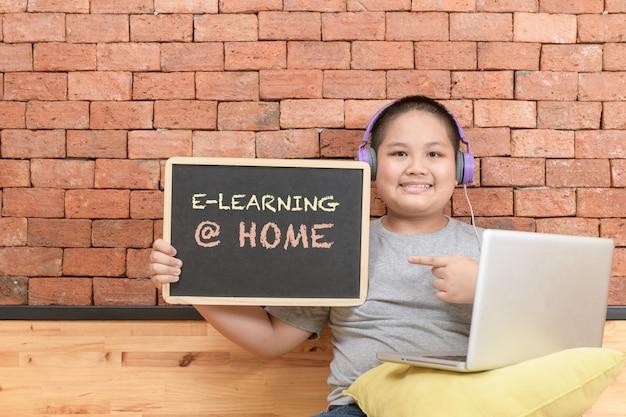 Otyły chłopiec uczeń nosić słuchawki nauki online i pokazuje tablica.