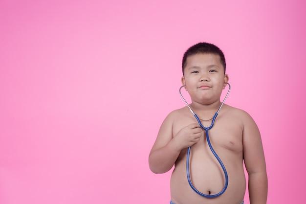 Otyły chłopiec z nadwagą na różowym tle.