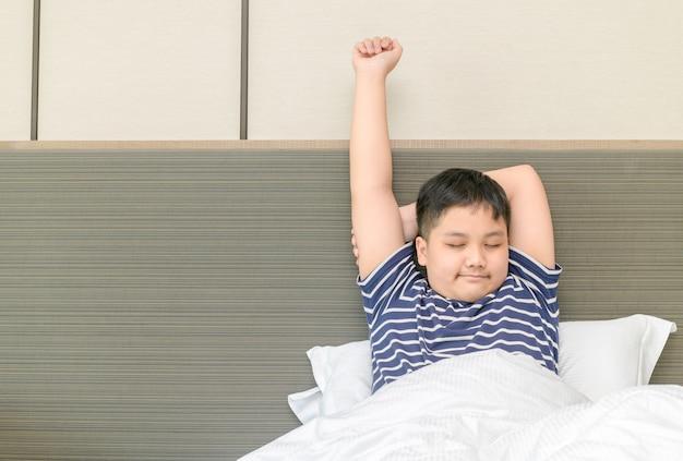 Otyły gruby chłopiec budzi się i wyciąga na łóżku rano, koncepcja opieki zdrowotnej i dzień dobry