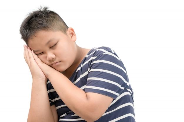 Otyły gruby chłopiec sen odizolowywający na białym tle