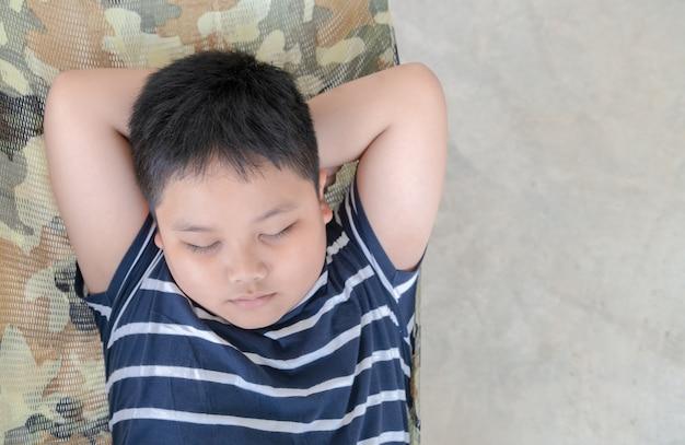 Otyły gruby chłopiec spać na kołysce w parku