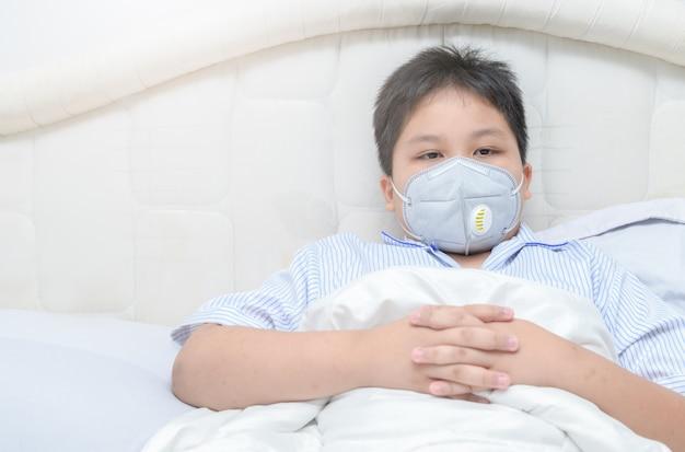 Otyły gruby chłopiec w masce przeciwpyłowej pm2.5