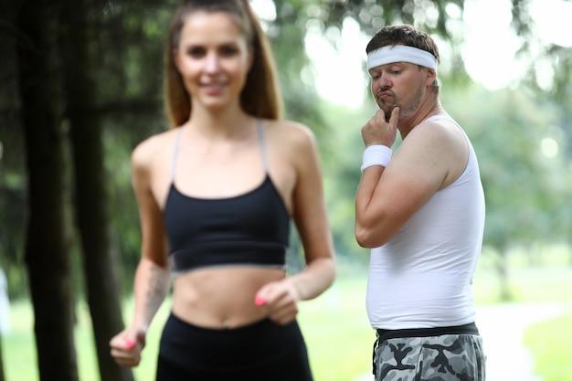 Otyły mężczyzna robi poranny jogging w parku