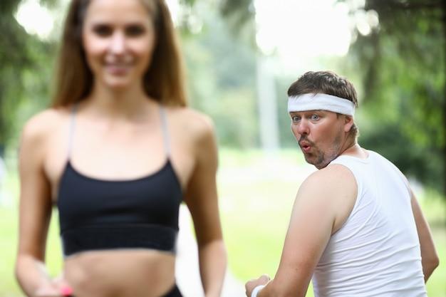 Otyły mężczyzna robi rano jogging w parku