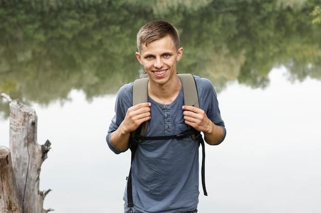Oung chłopiec ono uśmiecha się przy kamerą blisko jeziora