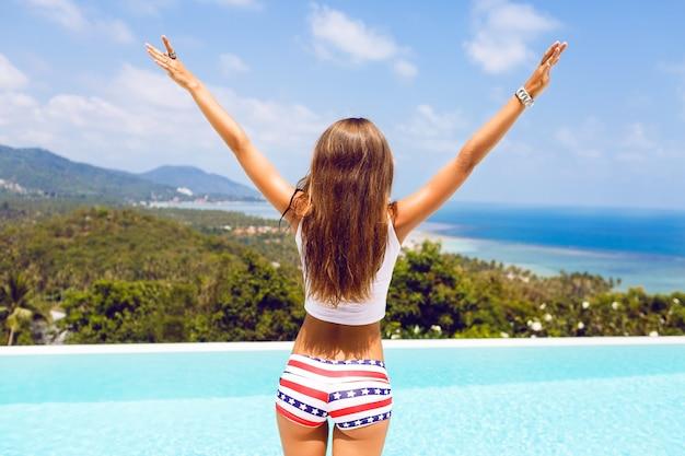 Outdoorowy portret kobiety o idealnym ciele w seksownych szortach, unosząc ręce w powietrzu i ciesząc się wolnością na niesamowitej tropikalnej wyspie. doskonały widok na ocean i góry