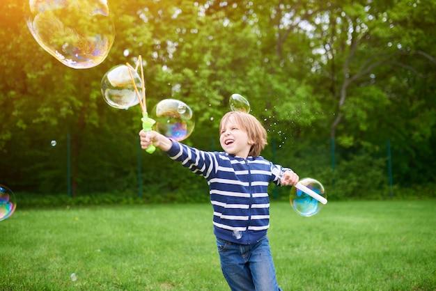 Outdoors portret śliczna preschool chłopiec dmucha mydlanych bąble na zielonym gazonie