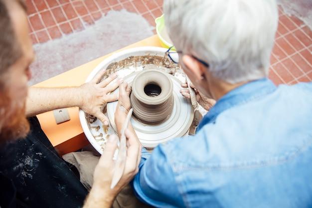 Over view at senior woman przędzenia gliny na kole z nauczycielem w klasie ceramiki
