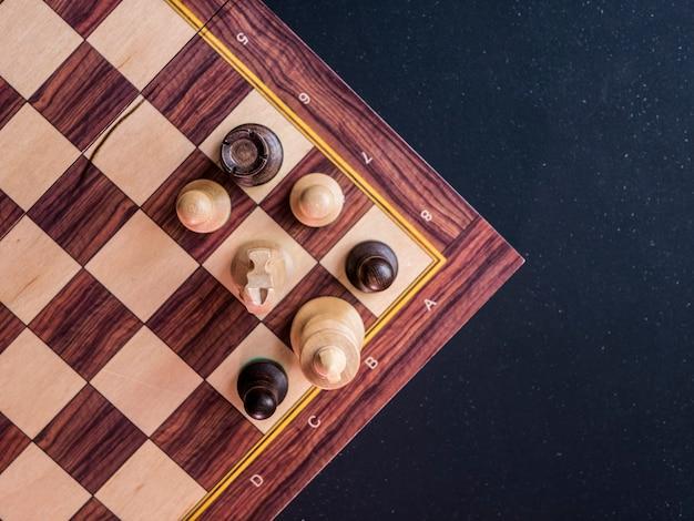 Overhead kopia miejsce szachownicy na czarnym ciemnym stole
