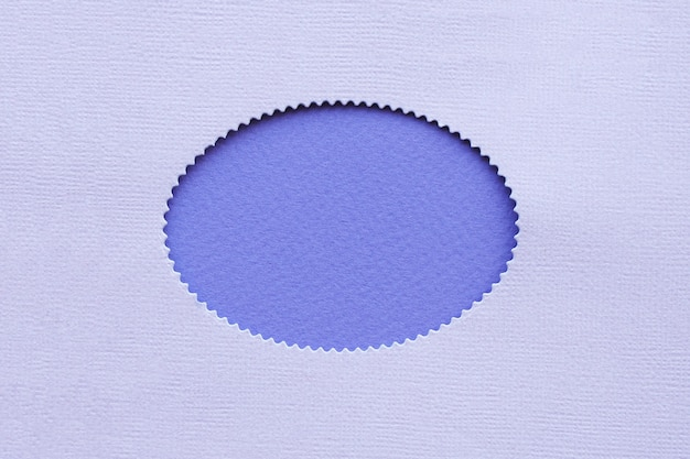 Owalna dziura z falistymi krawędziami z bzu na fioletowym tle papieru.
